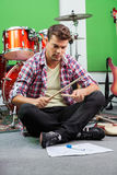Hombre que practica con los palillos mientras que se sienta en piso imagen de archivo