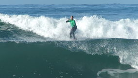 Hombre que practica surf en una onda en California metrajes