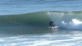 Hombre que practica surf en una onda grande en California en la cámara lenta
