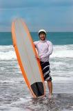 Hombre que practica surf feliz en la isla de bali Foto de archivo libre de regalías
