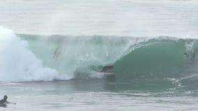 Hombre que practica surf una onda de la tubería en Santa Cruz California metrajes