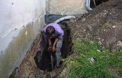 Hombre que prepara el agujero en la tierra para la instalación de la nueva película tachonada como aislamiento contra la humedad  Imagen de archivo