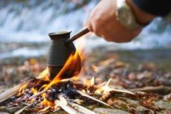 Hombre que prepara el café en hoguera Foto de archivo libre de regalías
