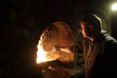 Hombre que prepara el fuego en estufa foto de archivo