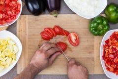 Hombre que prepara verduras en la cocina Imágenes de archivo libres de regalías
