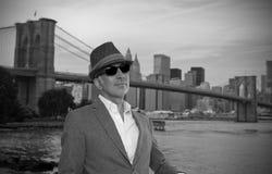 Hombre que presenta delante del puente de Brooklyn Foto de archivo