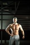 Hombre que presenta en gimnasio Fotografía de archivo libre de regalías