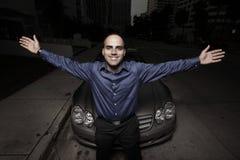 Hombre que presenta por un coche en la noche Imágenes de archivo libres de regalías