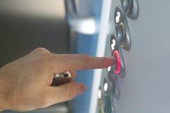 Hombre que presiona el botón de la elevación, cierre de la mano para arriba imágenes de archivo libres de regalías