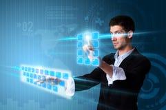 Hombre que presiona los botones de la pantalla táctil en azul Foto de archivo libre de regalías