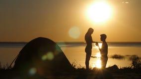 Hombre que propone a la mujer querida en la playa en la puesta del sol almacen de video