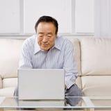 Hombre que pulsa en la computadora portátil Fotografía de archivo libre de regalías