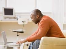Hombre que pulsa en la computadora portátil en sala de estar Fotos de archivo libres de regalías