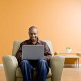Hombre que pulsa en la computadora portátil en sala de estar Imágenes de archivo libres de regalías