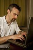 Hombre que pulsa en una computadora portátil Fotos de archivo libres de regalías