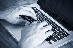 Hombre que pulsa en una computadora portátil Imágenes de archivo libres de regalías