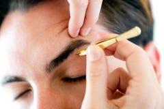 Hombre que quita los pelos de la ceja con extraer con pinzas fotos de archivo libres de regalías