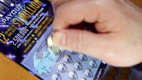 Hombre que rasguña el boleto de lotería almacen de metraje de vídeo