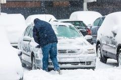 Hombre que raspa nieve congelada de las ventanillas del coche fotografía de archivo
