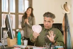 Hombre que reacciona negativamente a la tarjeta del día de San Valentín del compañero de trabajo foto de archivo
