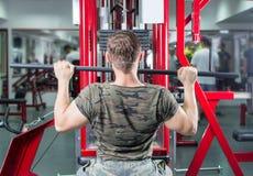 Hombre que realiza la desconexión del lat en el gimnasio Fotografía de archivo