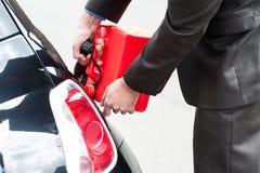 Hombre que reaprovisiona su coche de combustible Imagenes de archivo