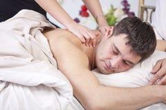 Hombre que recibe masaje en cama Fotos de archivo