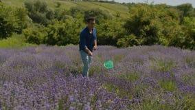 Hombre que recoge mariposas con la red en campo almacen de metraje de vídeo