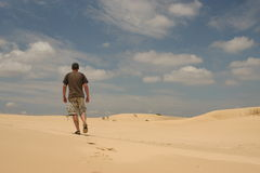 Hombre que recorre en desierto Imagenes de archivo