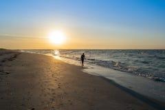 Hombre que recorre en la playa imagenes de archivo