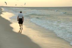 Hombre que recorre en la playa Fotografía de archivo