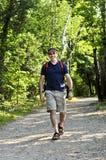 Hombre que recorre en rastro del bosque Imagen de archivo libre de regalías
