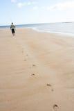 Hombre que recorre a lo largo de la pesca que lleva Rod de la orilla Fotografía de archivo libre de regalías