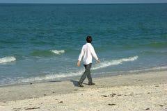 Hombre que recorre a lo largo de la playa Foto de archivo libre de regalías