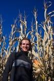 Hombre que recorre más allá de campo de maíz Imagenes de archivo