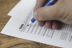 Hombre que rellena el impreso de impuesto de los E.E.U.U. formulario de impuesto nosotros concepto del terraplén de la mano de la fotografía de archivo libre de regalías
