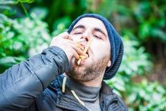 Hombre que rellena su cara con las patatas fritas Foto de archivo libre de regalías
