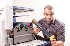 Hombre que repara el cartucho de tinta cambiante de la impresora de color foto de archivo libre de regalías