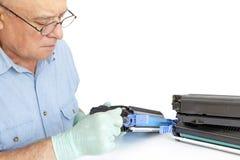 Hombre que repara el cartucho de toner foto de archivo