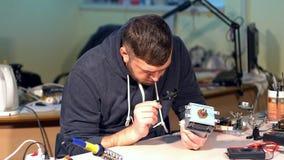 Hombre que repara el dispositivo roto en taller almacen de video