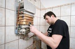 Hombre que repara el horno de gas Foto de archivo libre de regalías