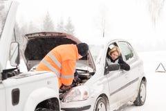 Hombre que repara el invierno de la ayuda de la nieve del coche de la mujer Imagen de archivo libre de regalías
