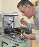 Hombre que repara el ordenador Foto de archivo libre de regalías