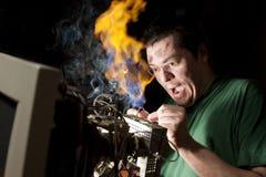 Hombre que repara el ordenador en el fuego Imágenes de archivo libres de regalías