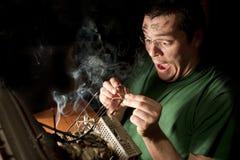 Hombre que repara el ordenador en el fuego Fotos de archivo