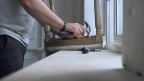 Hombre que repara la silla en el cuarto metrajes