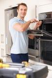 Hombre que repara a Oven In Kitchen nacional Imágenes de archivo libres de regalías