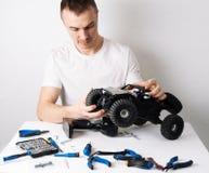 Hombre que repara un cochecillo radio-controlado del coche modelo En la tabla son las herramientas para la reparación imágenes de archivo libres de regalías