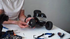 Hombre que repara un cochecillo radio-controlado del coche modelo En la tabla son las herramientas para la reparaci?n almacen de video