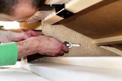 Hombre que repara un sofá Fotografía de archivo libre de regalías